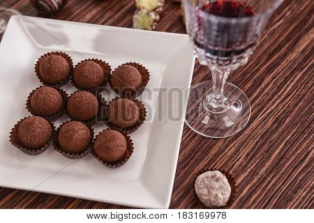 Chocolate candies and glass of red wine on wooden background