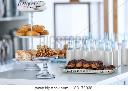 Tasty desserts and bottles with milk on table