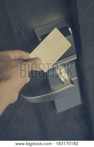 Hand holding keycard hotel front electronic sensor of room door