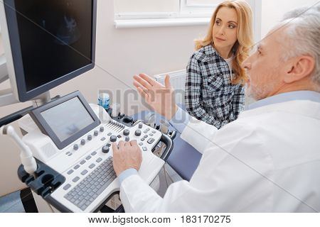 Discussing result of ultrasonic scanning . Helpful qualified senior sonographer working in the clinic and consulting the patient while providing ultrasonic scanning