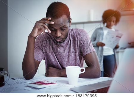 Unhappy african american family financial stress: black man sitting at kitchen reading notification informing that bank denied to prolong loan term his wife standing with bills in background