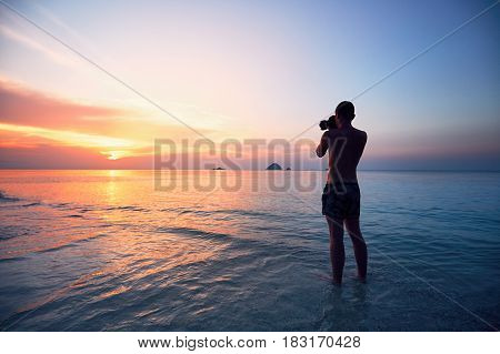 Silhouette of the young photographer (tourist). Photo shooting during amazing sunset on the tropical beach.