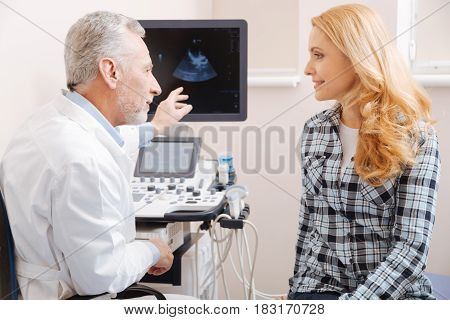 Explaining all details. Aged delighted experienced sonographer working in the hospital and consulting the patient while providing ultrasound body scanning