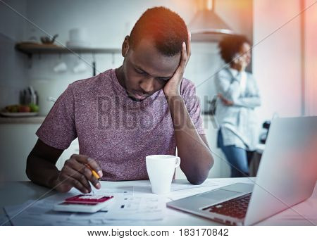 Sad african american man sitting with laptop at kitchen table looking at bills counting expenses planning how to pay rent stressed wife calling to bank at background. Household budget concept