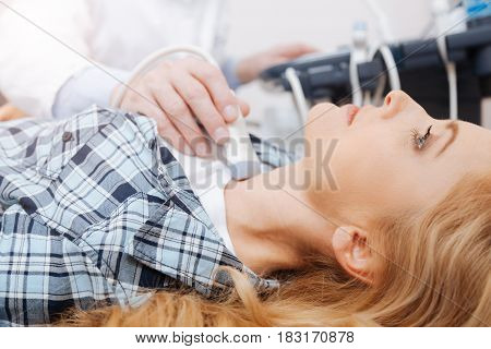 Getting ultrasound checkup of my body. Concentrated motionless attractive woman visiting doctor and lying on the medical couch while medic providing thyroid scanning