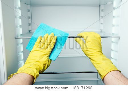 Man's Hand Cleaning White Fridge With Blue Rag