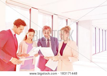 Businessmen and businesswomen discussing over documents in new office