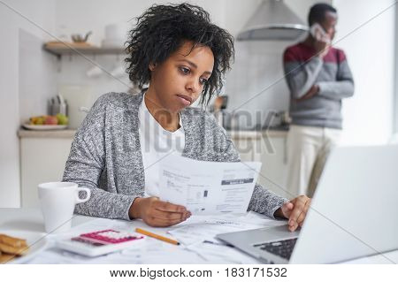 Beautiful young dark-skinned woman keeping hand on touchpad of laptop computer looking at screen with serious concentrated expression paying bills online while her husband making call to bank