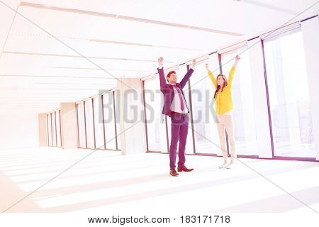Full length of successful businessman and businesswoman with hands raised in empty office