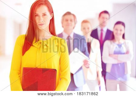 Portrait of confident young businesswoman with team in background at office
