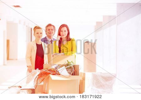 Portrait of business people standing by stacked cardboard boxes at new office