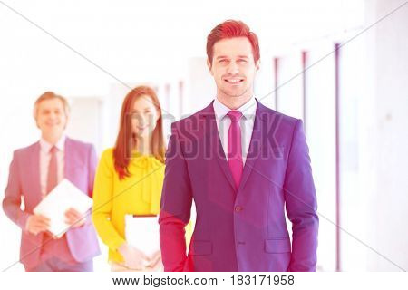 Portrait of confident young businessman with team in background at office
