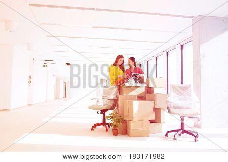 Businesswomen unpacking cardboard boxes in new office