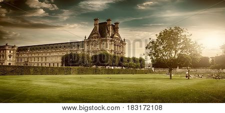 PARIS, FRANCE - AUGUST 26, 2016. View of  Louvre Palace and its green park in summer at sunset