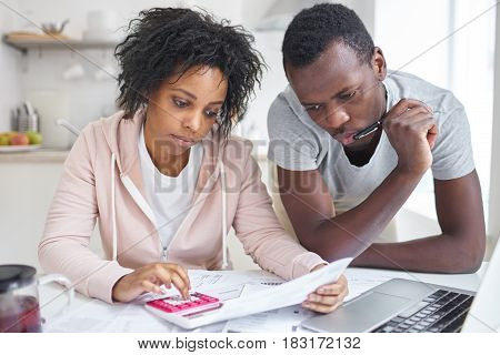 Stressed African-American couple working through paperwork together calculating expenses trying to save some money managing family finances sitting at kitchen table with laptop and calculator