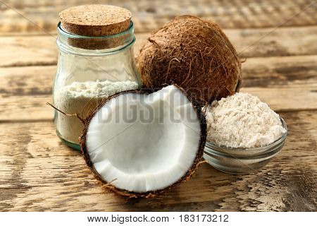 Bowl with coconut flour and half of nut on wooden background