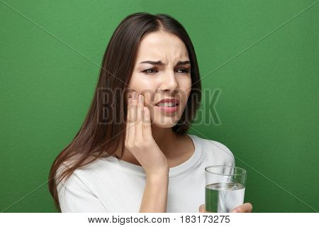 Beautiful young woman with medicine  suffering from toothache on color background