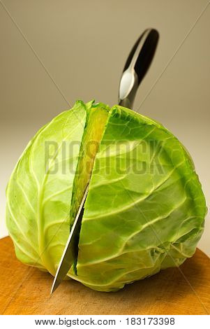 A kitchen knife cuts cabbage on the Board.