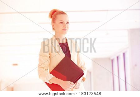 Young businesswoman holding file while looking away in new office
