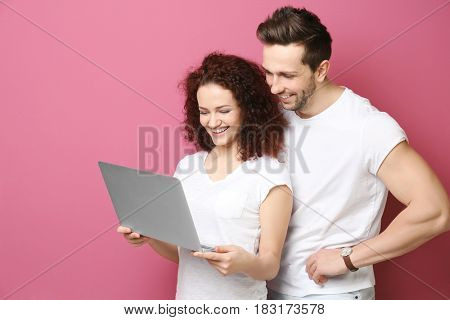 Happy young couple with laptop on color background