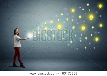 Caucasian woman holding lightbulbs, which are floating away from her hands