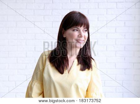 Beautiful mature woman near brick wall