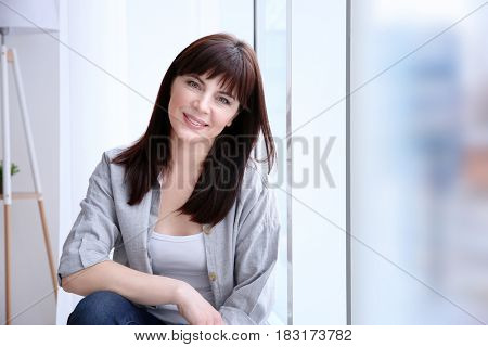 Beautiful mature woman near window at home
