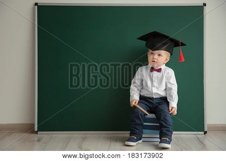 Cute little boy with pointer and magister hat sitting on pile of books near blackboard