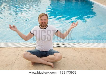 Young man with a beard meditates and a background of the pool. Pleasant rest at the hotel.