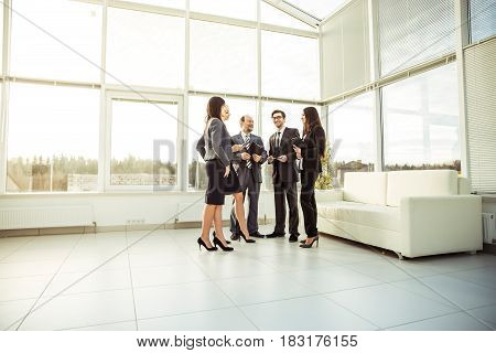business team standing in the spacious lobby of the modern office.the photo has a empty space for your text