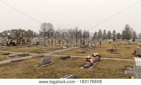 rustic midwestern cemetery on a cold and foggy day