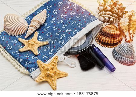 Small anchor printed cosmetic bag with powder brush and pencils and shells and starfish around