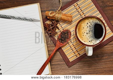 Top view still life with a cup of espresso coffee different condiments on the bamboo mat and a lined notebook with pen