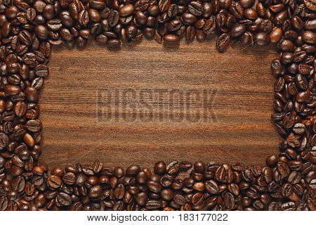 Frame of roasted coffee beans on the rude wooden table