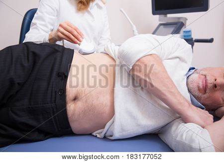 Using modern equipment for detecting tumor. Bearded peaceful retired patient lying on the medical couch and getting ultrasound abdomen monitoring while sonographer using ultrasound machine