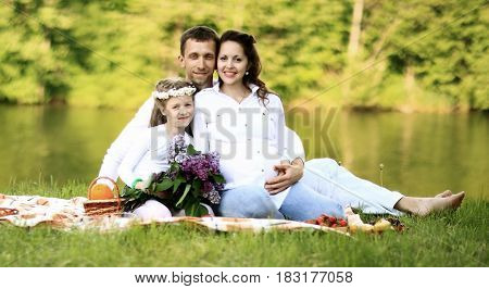 happy father of a daughter and a pregnant mom in the picnic.