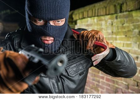 Gangster Holding Crowbar While Pointing With Gun At Night