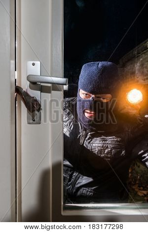 Intruder Holding Torch While Trying To Open Window With Crowbar