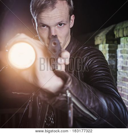 Special Agent in twilight, dusk pointing his gun and torch on suspect in an alley