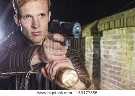 Alert law enforcement officer with handgun and torch ready for action
