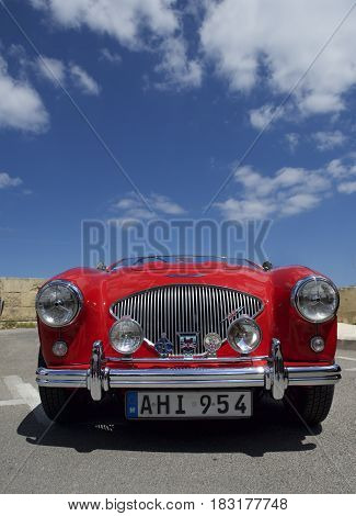 Valletta, MALTA - apr 23, 2017: vintage classic retro cars parked in Hastings Gardens in Valletta, Malta.Artistic photo of old red car with nice sky background
