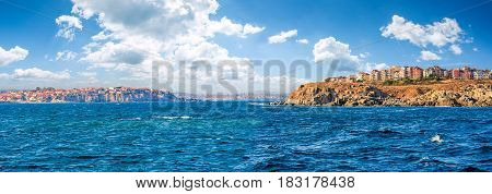 composite summer seascape. panoramic view of old resort town on a rocky cliff above the seashore. blue and calm water in the sea