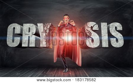 A businessman in a red cape and a mask kicking concrete letters reading 'Crysis' with his foot. Overcoming difficulties. Business and competition. Financial troubles.