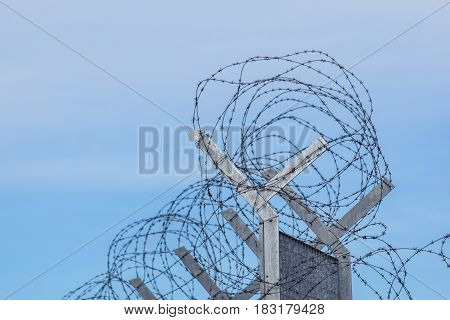 Razor Barbed wire against a blue sky, closeup .