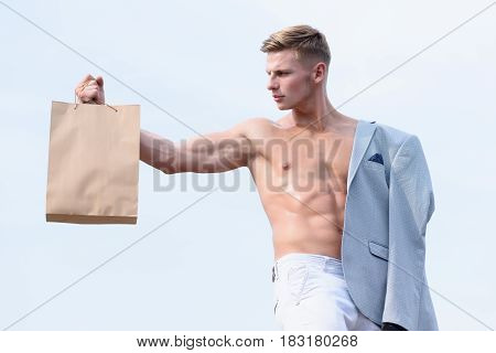 Man Holding Shopping Bag On Sky Background With Serious Face