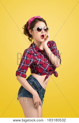 Lovely Woman Retro Portrait With Pin-up Make-up And Hairstyle Wearing Sunglasses Posing Over Yellow