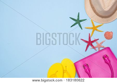 Summer Concept. Pink Handbag With Accessories On Light Blue Background