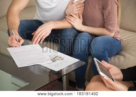 Renting and tenancy concept. Close up of couple in love signing rental agreement sitting on couch with female realtor, starting living together, housing rent, residential property lease contract