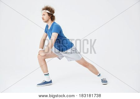 Man in blue shirt, grey shorts, long socks and blue sneakers, lunging forward, looking straight