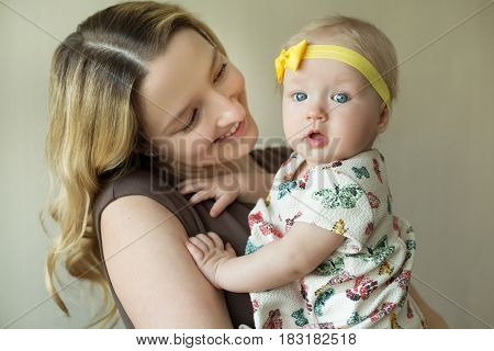 Happy mother of European appearance with a little daughter girl in her arms